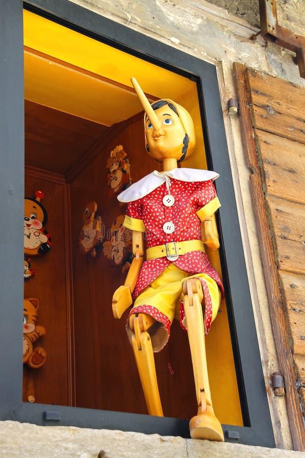 Pinocchio en la tienda del edificio de la ventana de juguetes de madera foto de archivo