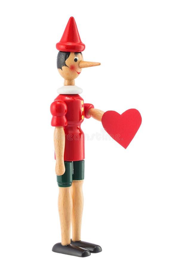 Pinocchio leksakstaty med hjärta som isoleras på vit royaltyfri foto