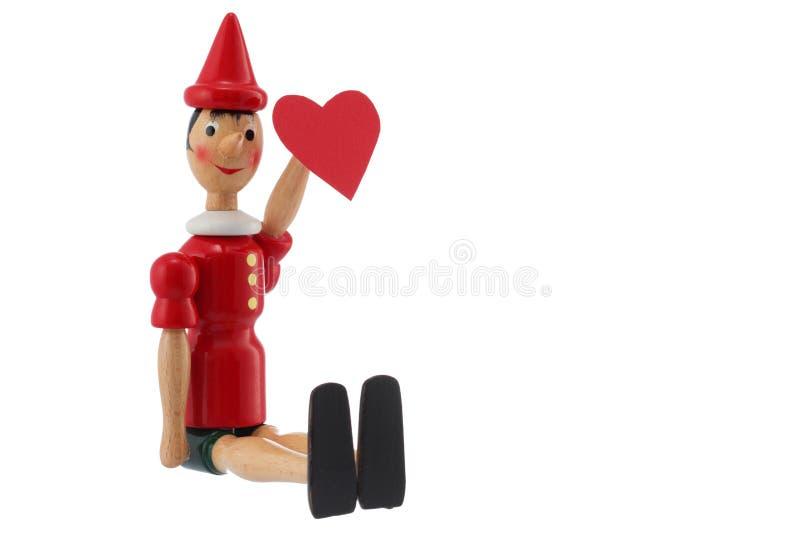 Pinocchio leksakstaty med hjärta som isoleras på vit royaltyfria bilder