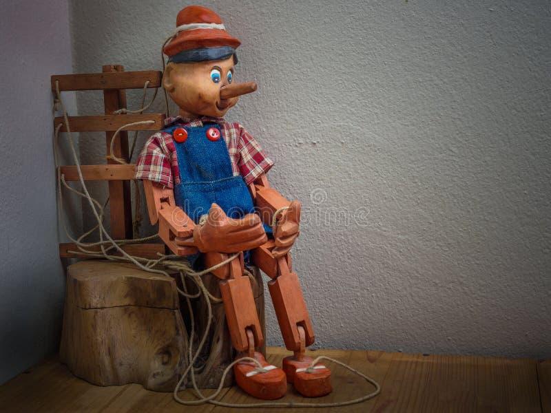 Pinocchio-Marionette gemacht vom Holz im Weinleseton stockfotos