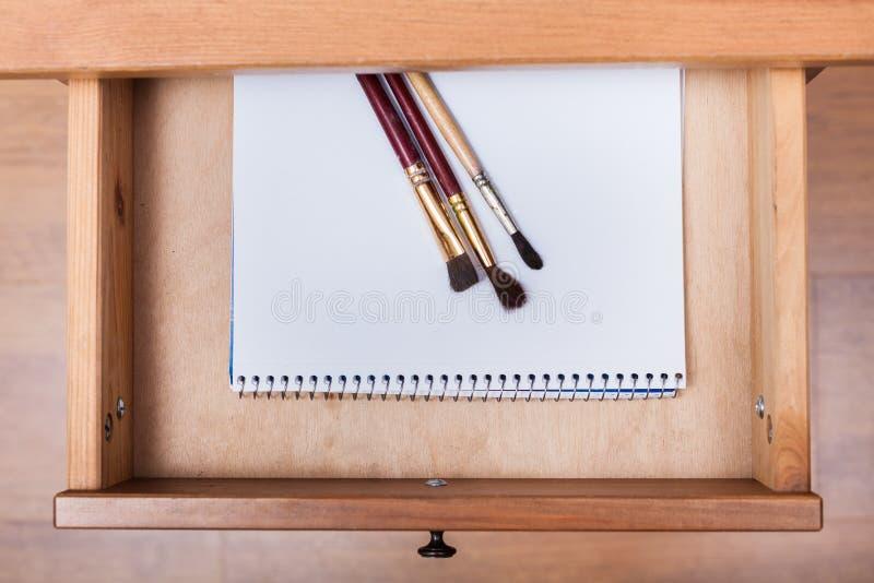 Pinsel auf Zeichnungsalbum im offenen Fach stockbild