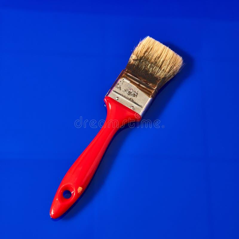 Pinsel für Wohnungsreparatur lokalisiert auf einem Blau lizenzfreie stockfotografie