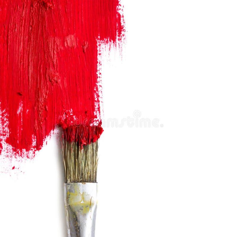 Pinsel malt die weiße Oberfläche mit roter Farbe, Konzeptrepräsentanten lizenzfreie stockfotos