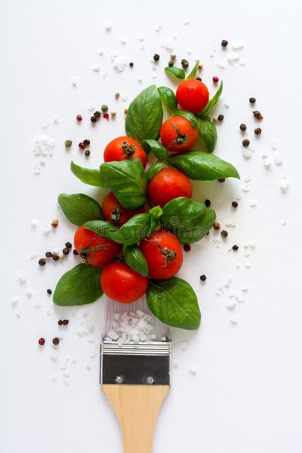 Pinsel und Klecks von Ketschupbestandteilen für das Kochen der Soße: Tomate, Basilikum, Pfeffer, Salz Lebensmittelkunstkonzept stockfoto
