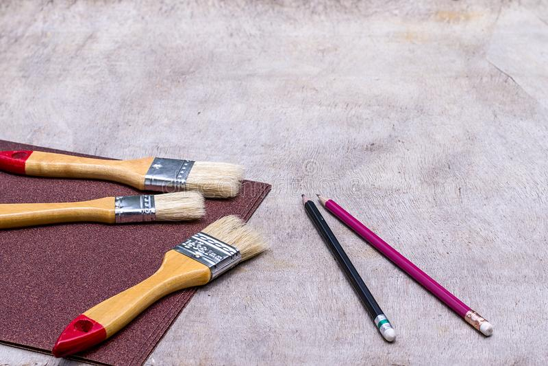 Pinsel und Sandpapier und Bleistift auf altem Holzfußboden, bereiten Holzoberfläche vor stockfoto