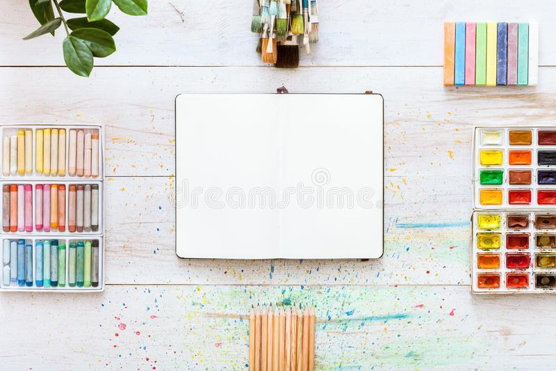 Pinselsatz, Paintbox mit Aquarellen, Zeichenstifte, Bleistifte und offenes Notizbuchpapier auf dem weißen hölzernen Hintergrund,  stockfotos