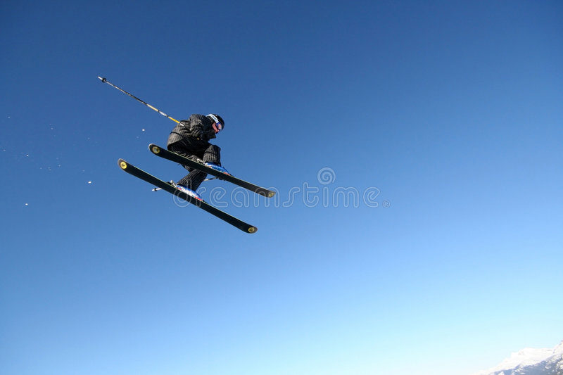 Pinstripe Suit. A skier in a business-like pinstripe suit flies through the air in Whistler, BC royalty free stock photo