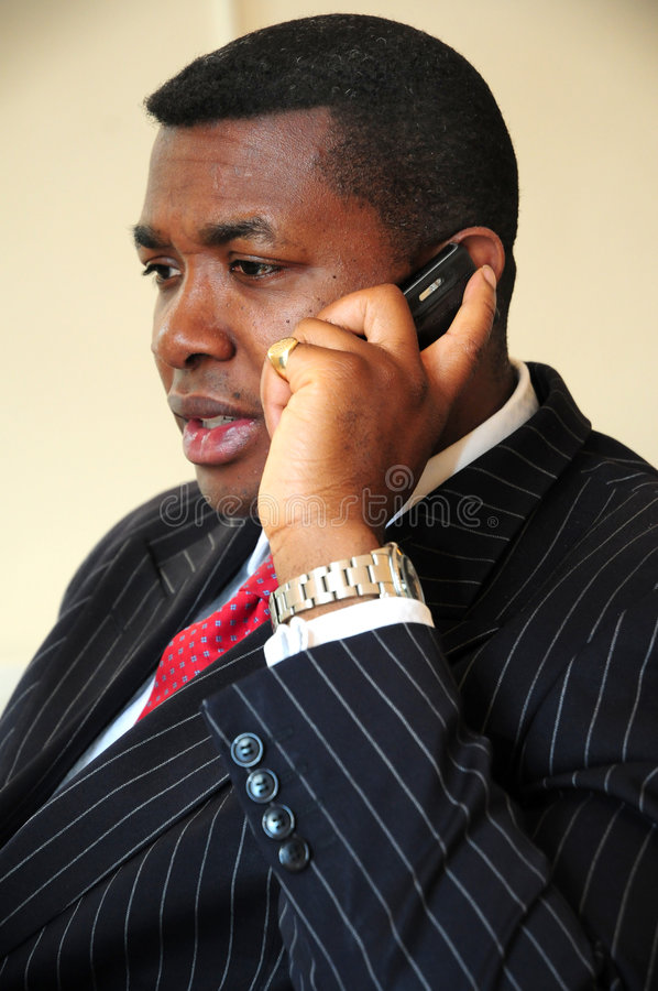Pinstripe suit man on phone. A pinstriped suited afro caribbean man with red tie on phone stock image