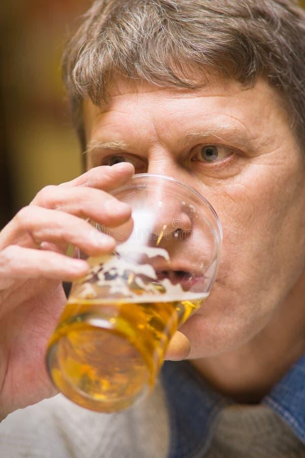 Pint. Mature man drinking beer; selective focus stock image