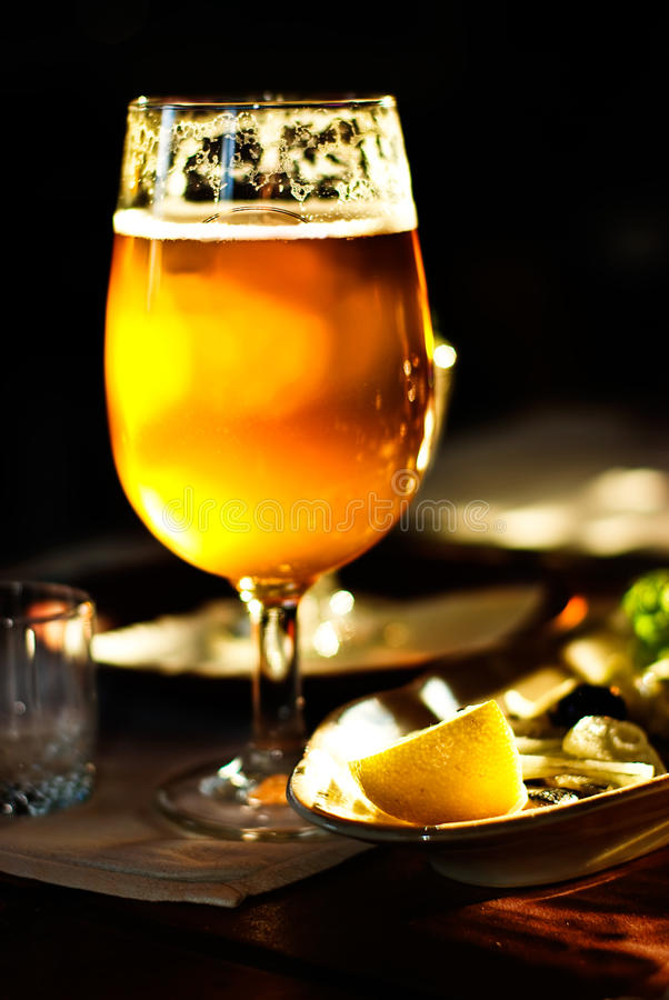 A Pint of Beer. On a table and food background stock image