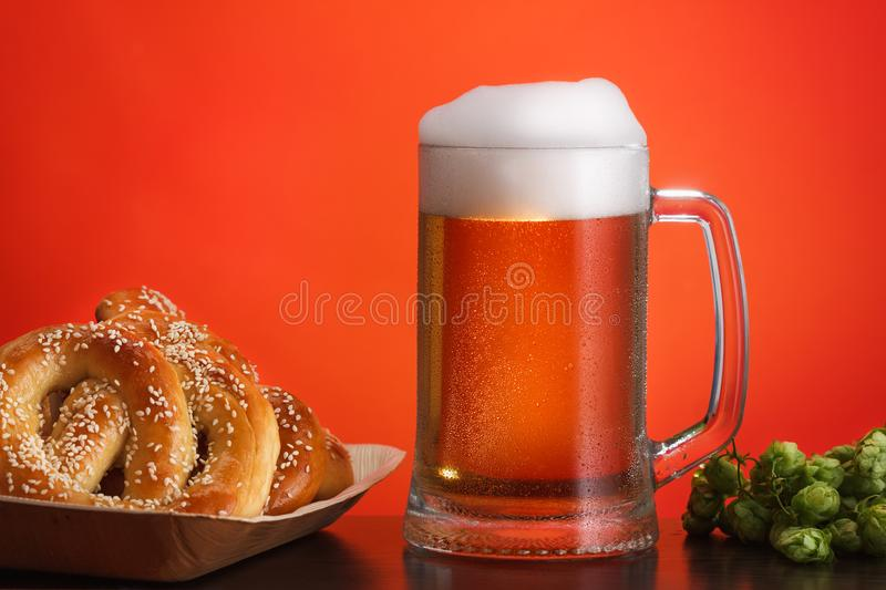 Pint of beer with ingredients for homemade beer on red with pretzel stock image