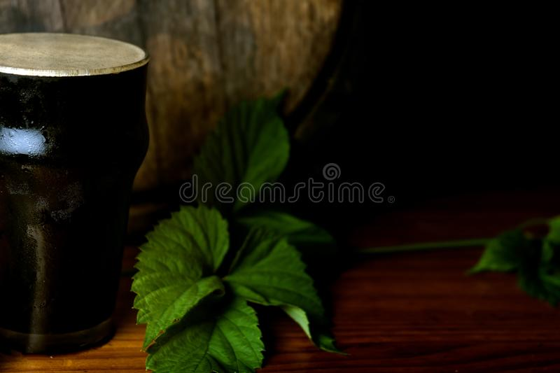 Pint dark beer nicely with a leaf of hops on the background of the barrel. Close up stock photography