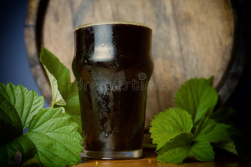 Pint dark beer nicely with a leaf of hops on the background of the barrel. Close up stock photos