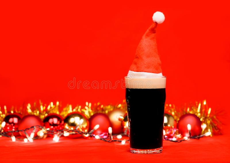 Pint-Glas Ale des dunklen Bieres oder des Stouts mit rotem Sankt-Hutweihnachtslichtflitter und -lametta auf rotem Hintergrund stockfotografie