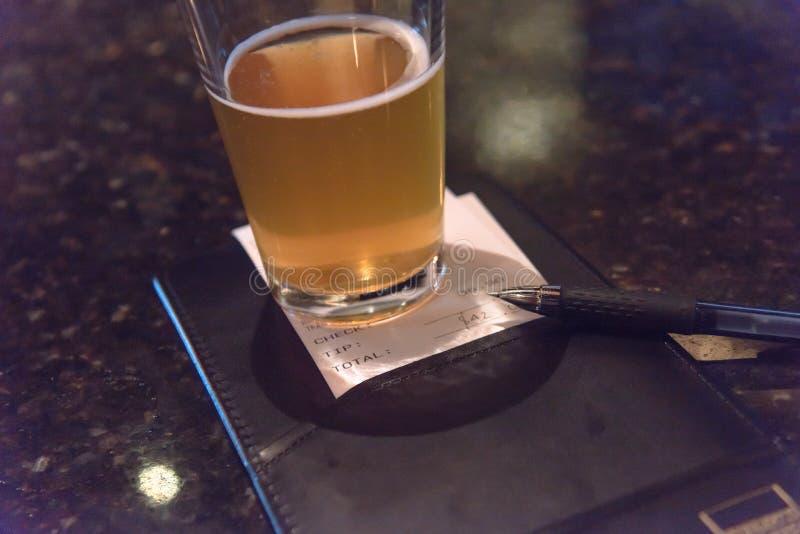 Pint-Glas-Bier- und -lederWechselinhaber mit Restaurant überprüfen stockfoto