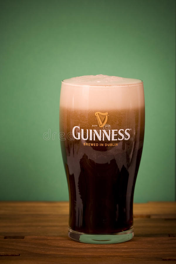 Pint of Guinness. A pint glass freshly filled with Guinness - head is continuing to build - Guinness is a popular Irish dry stout that originated in the brewery