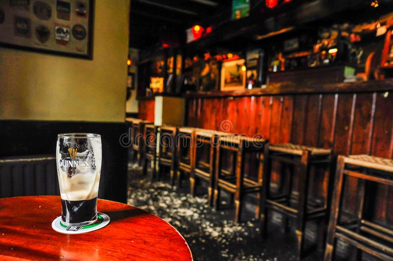A Pint of Guinness. A well enjoyed pint Guinness beer rests in a quiet pub in Kinsale, Ireland royalty free stock images