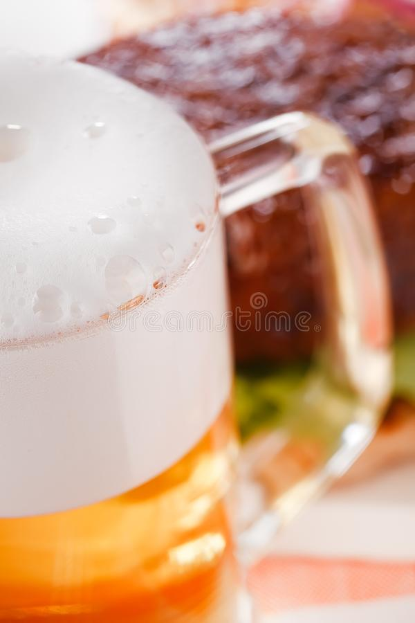 Pint of lager beer with burger on background royalty free stock photo
