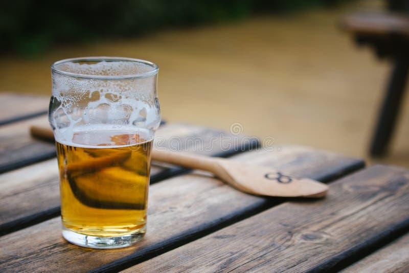 Pinta bebida mitad de cerveza dorada con una cuchara de madera en el fondo i imagen de archivo