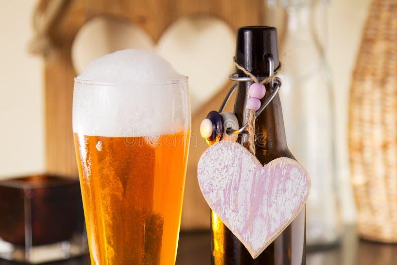 Pinta de cerveza espumosa con un corazón imagenes de archivo
