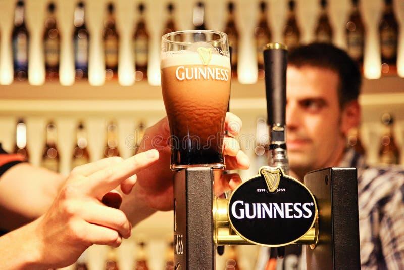 Pinta de Guinness en el contador en la cervecería del almacén de Guinness con señalar del finger y la persona en el fondo imagenes de archivo