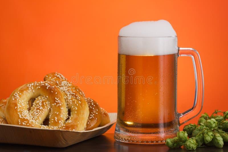 Pinta di birra con gli ingredienti per birra casalinga su rosso con la ciambellina salata fotografie stock