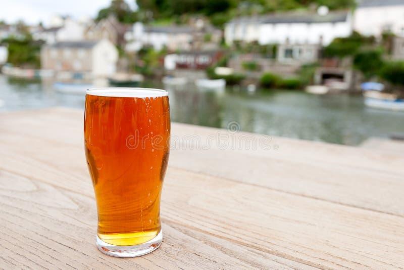 Pinta di birra inglese reale fuori di un Pub del villaggio della riva del fiume fotografia stock libera da diritti