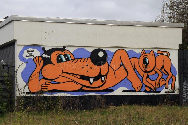 Pintada de la calle con el perro y el gato divertidos en la pared en Copenhague imagenes de archivo