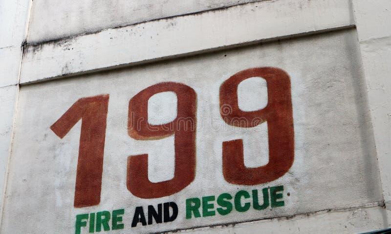 Pintada de la pared que ofrece un número de teléfono de 3 dígitos imagen de archivo