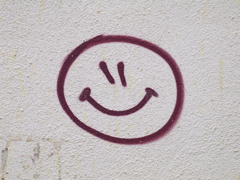 Pintada sonriente de la cara dibujada en la pared foto de archivo