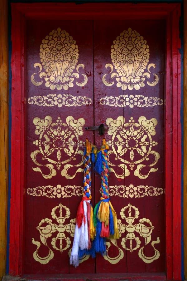 Pintado con la puerta roja de los símbolos budistas tradicionales con las bufandas sagradas atadas de los hadags como manijas en  foto de archivo libre de regalías