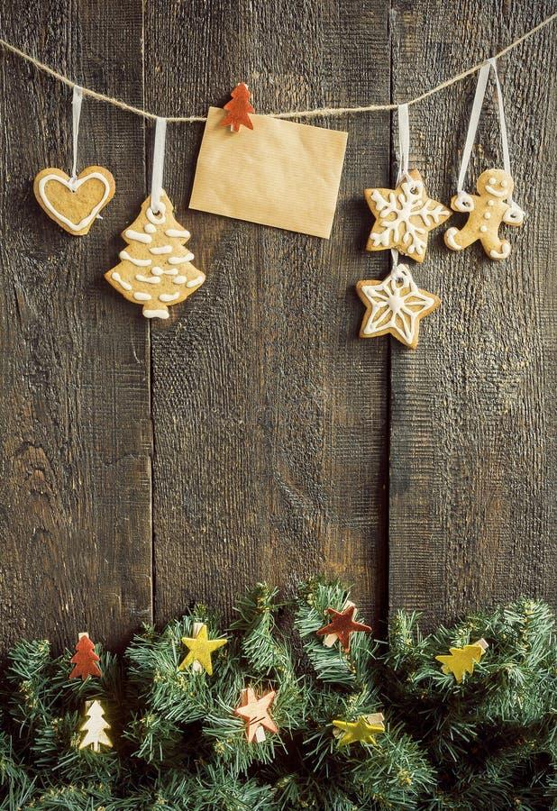 Pintado por galletas del jengibre y una tarjeta en blanco en una cuerda sobre el fi imágenes de archivo libres de regalías