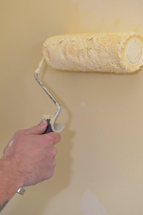 Pintando a parede com um rolo imagens de stock royalty free