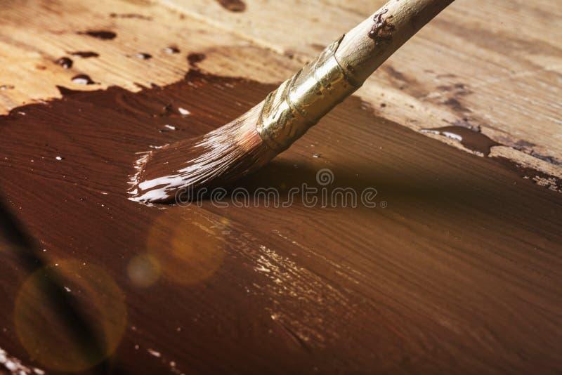 Pintando um quadro de madeira com cor do chocolate imagens de stock royalty free