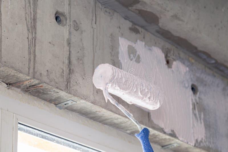 Pinte el rodillo y la cartilla en la pared sobre la ventana Concepto de reparar las casas, apartamentos, preparando las paredes p foto de archivo