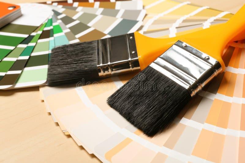 Pinte escovas e paletas de cores na tabela imagens de stock