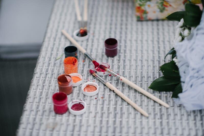 Pinte escovas e pinturas para tirar na tabela fotografia de stock