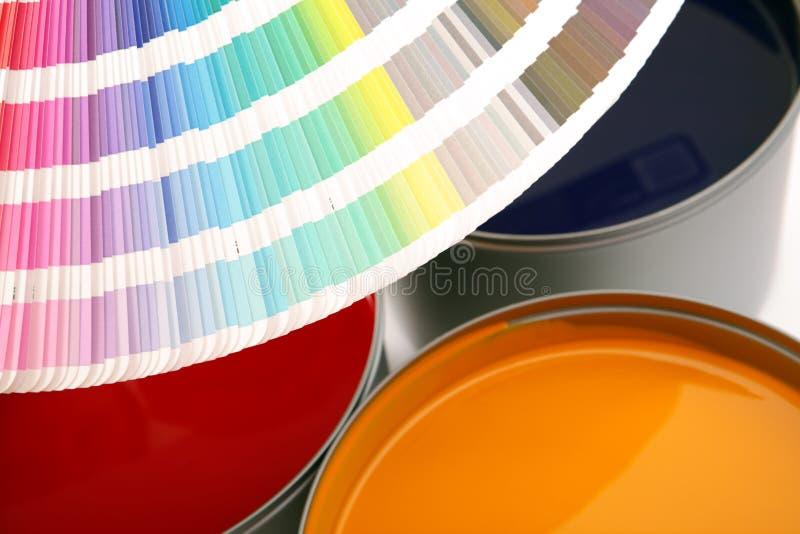 Pinte la muestra con las latas de la pintura fotos de archivo