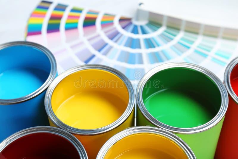 Pinte las latas y las muestras de la paleta de colores en la tabla imagen de archivo