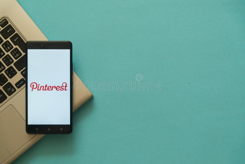 Pinterest logo on smartphone placed on laptop keyboard. stock photo