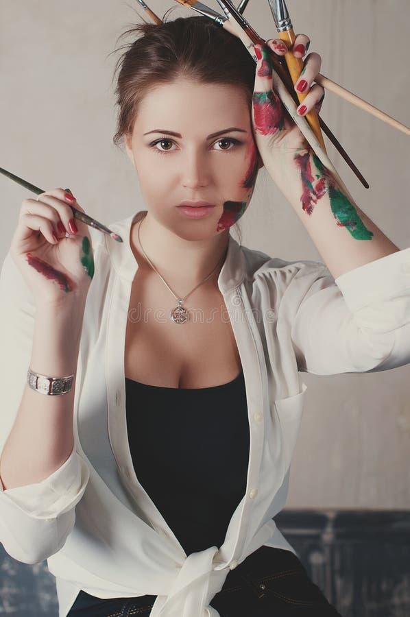 Pintor bonito da jovem mulher em seu estúdio fotografia de stock royalty free