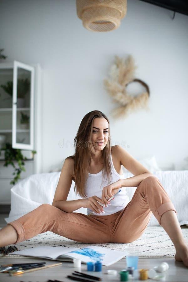 Pintor bonito novo da mulher em casa fotos de stock royalty free