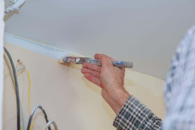 Pintor com pintura do pincel com paredes e tetos foto de stock