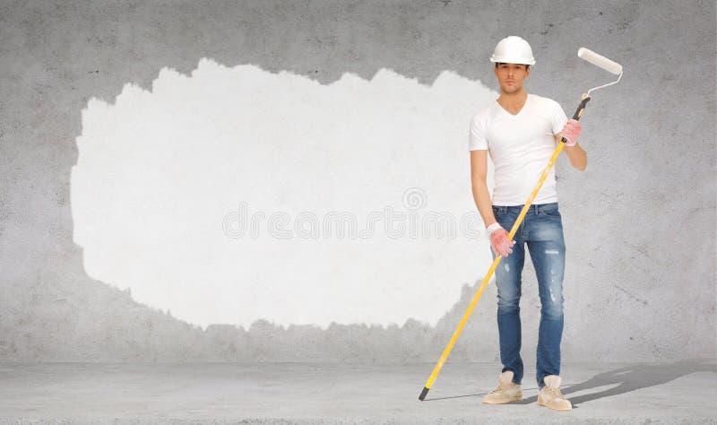 Pintor considerável no capacete com rolo de pintura fotografia de stock