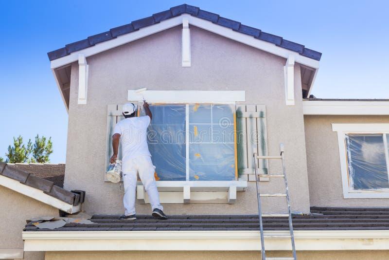 Pintor de casa Painting a guarnição e os obturadores da casa imagens de stock