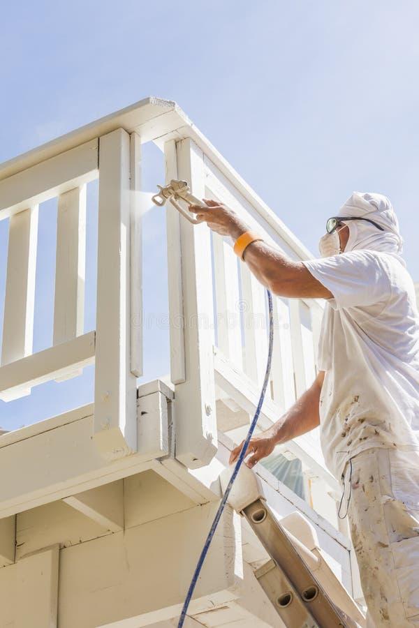 Pintor de casas de trabajo duro Spray Painting una cubierta de un hogar fotografía de archivo