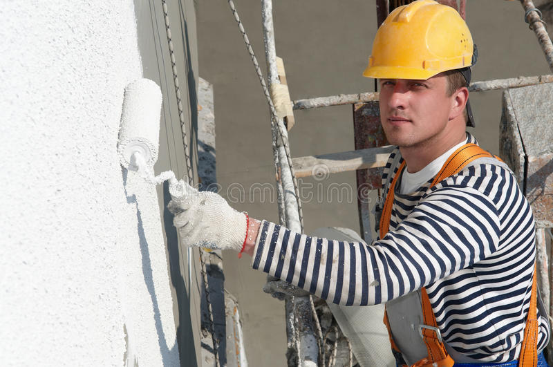 Pintor de la fachada del constructor en el trabajo imagenes de archivo