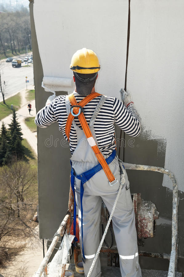 Pintor de la fachada del constructor en el trabajo foto de archivo