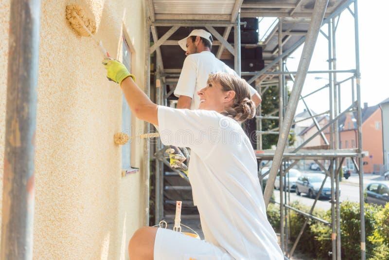 Pintor de la mujer que pinta una pared con la pintura amarilla imagen de archivo libre de regalías