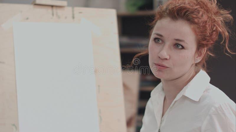 Pintor de sexo femenino joven cerca del caballete que describe proceso creativo foto de archivo